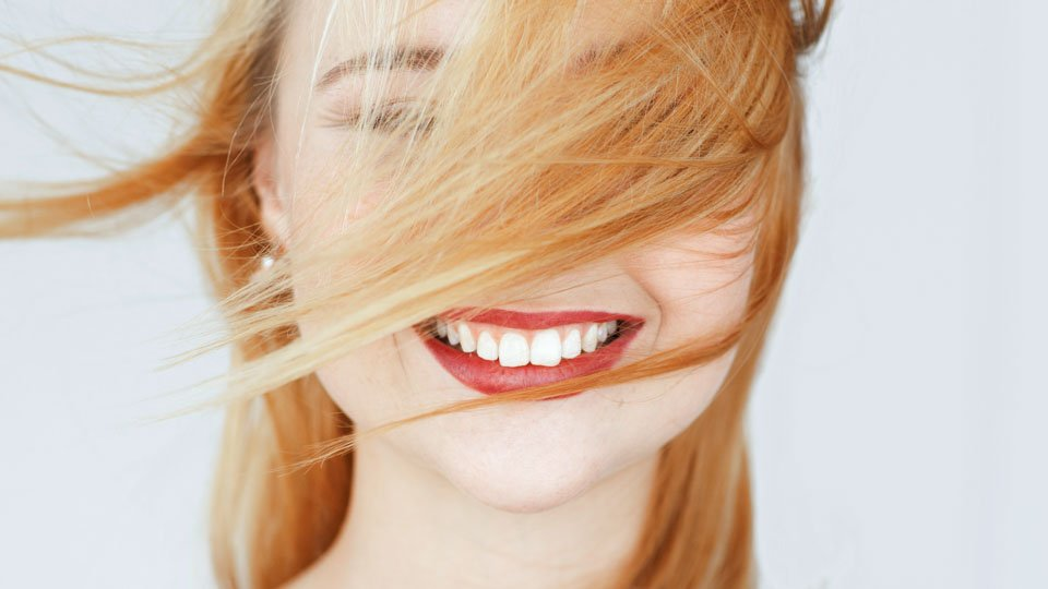 Perfect white smile of red-haired girl, close-up. Widely smiling happy carroty woman portrait. Good dentist in Helsinki, teeth care, whitening concept